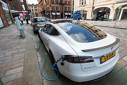 Tesla electric car charging on street in Merchant City district in Glasgow, United Kingdom