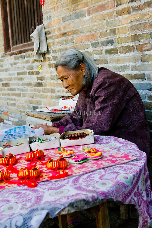 The ancient village of Yangmei is approximately 30 kilometres from the provincial capital of Nanning.  Ms Huang making tiny embroidered shoes in the grounds of Huang Manor in Huangyao.