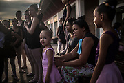 The mother of Melissa Barboza ties her daughter's dress  before an outdoor class    in Manguinhos neighbourhood in Rio de Janeiro, Brazil, Monday, June 11, 2018. The Manguinhos community ballet has been a reprieve from the violence and poverty that afflicts its namesake neighborhood for hundreds of girls who have benefitted from free dance classes since 2012. (Dado Galdieri for The New York Times)