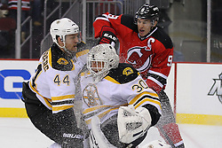 Jan 19; Newark, NJ, USA; New Jersey Devils left wing Zach Parise (9) and Boston Bruins defenseman Dennis Seidenberg (44) collide with Boston Bruins goalie Tim Thomas (30)  during the second period at the Prudential Center.