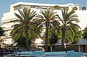 Israel, Tel Aviv 3 palm trees in Dizengoff circle in centre Tel Aviv. Hotel Cinema in the background