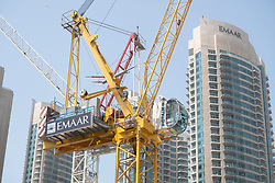 Construction crane on construction site building new high rise apartment towers in Downtown Dubai, UAE, United Arab Emirates,