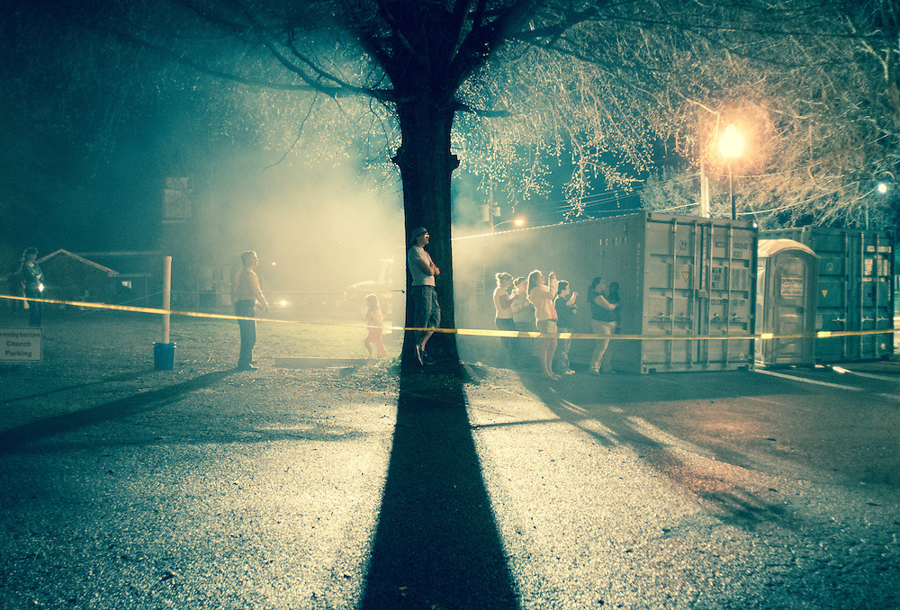 A middle-aged Caucasian male leans against an old tree at night on Rt. 64 in Pittsboro, NC. He is surrounded by smoke and bystanders watching the historic Pittsboro county courthouse burn in March, 2010.