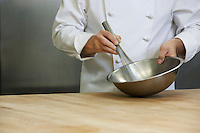 Male chef mixing ingredients using whisk mid section