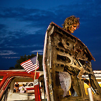 USA, Maryland, Mechanicsville, Man stands over hood of damaged truck after participating in Demolition Derby at Potomac Speedway