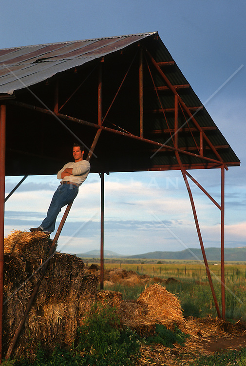 Man leaning on a pole in an open barn watching a sunset