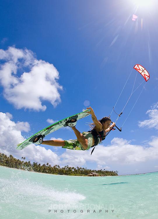 Professional kiteboarder Clarissa Hempel skies over beautiful lagoon in Bora Bora, french polynesia.