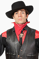 Young cowboy in black leather vest against white background