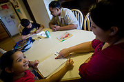 Dennis, center, and Sophia Sawyer, right, help their children, Frances, far left, and Daniel, center left, with their homework January 27, 2010 in Sacramento, Calif. The Sawyer family receives $540/month in CalWORKs assistance from the state of California. Dennis is currently unable to work while recovering from cancer, and Sophia hasn't been able to find work. Gov. Arnold Schwarzenegger has proposed eliminating the CalWORKs program in an effort to balance the state's budget. CREDIT: Max Whittaker for The Wall Street Journal.CABUDGET