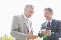 Happy businessmen discussing over mobile phone outdoors