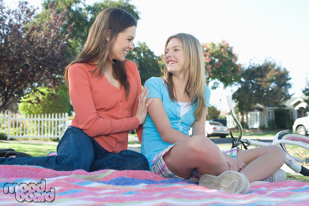 Mother and daughter sitting on picnic blanket