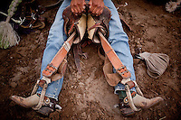 Navajo Nation Indian Rodeo.  A bronc rider prepares to ride with his saddle and dusty old boots and spurs. American Indian Cowboy