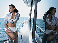 Young woman on yacht sitting on railing looking at ocean reflected in window glass