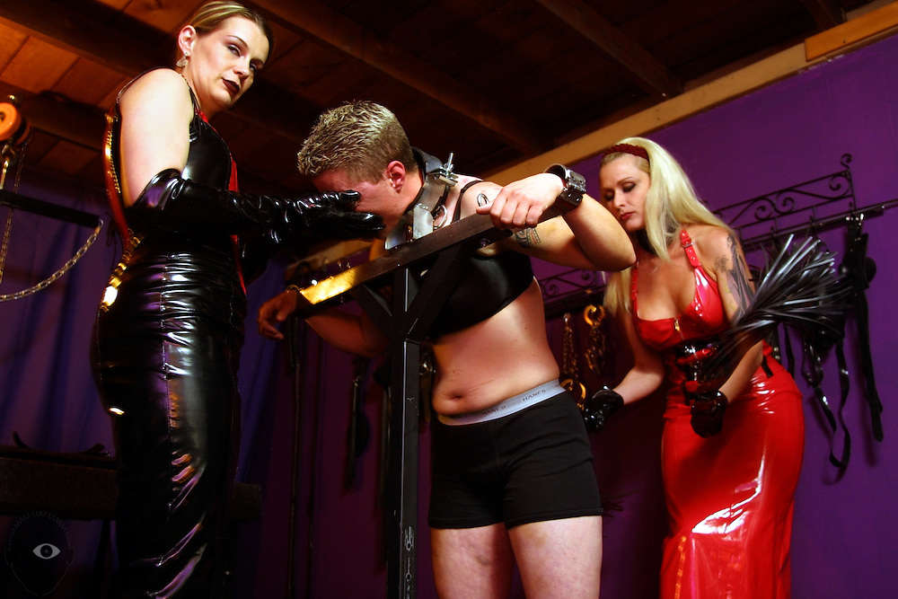 May 18, 2003 - Domina Goddess Severina Stern (right) uses a whip as her apprentice Soren Stern  (left) works the face  of submissive Trystan Askelson (center) in her SE Portland, Oregon, room she calls the dungeon. Many seek out their services which can feature time like this in a stock, lying on the rack or being locked in a cage. This city has one of the most numerous sex-related businesses per capita  in the United States.