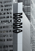 The large banner for MoMA hanging vertically outside the museum is reflected in the mirrored windows.