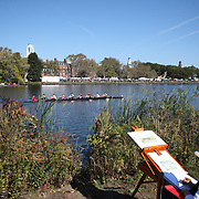 BOSTON, MASSACHUSETTS - OCTOBER 21: An artist works on the bank of the Charles river on a beautiful fall day as crews compete in The 53rd Head of the Charles Regatta on the Charles River which separates Boston and Cambridge, Massachusetts, USA. The Head of Charles, which began in 1965, attracts over 11,000 athletes from around the globe. The course is 3 miles (4,800 meters) long and stretches from the start at Boston University's DeWolfe Boathouse near the Charles River Basin, passing Harvard University to the finish just after the Eliot Bridge. Boston, Massachusetts. 21st October 2017. (Photo by Tim Clayton/Corbis via Getty Images)