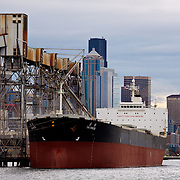 Grain ship taking on grain cargo at grain elevator, pier 86, with Seattle, Washington skyline in background