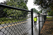 Manchester EMS officer/firefighter paramedic Chris Hickey looks for discarded needles along a fence outside of a playground on Mitchell St in Manchester, NH Wednesday, Aug. 10, 2016. <br /> To help combat Manchester New Hampshire's huge drug problem, anyone can walk into the main fire station seeking help, they'll get connected with a drug counselor and services. Something like 230 people have shown up in the first couple months and it's quickly spawning copy-cat programs.  <br />    (Cheryl Senter for The Wall Street Journal)