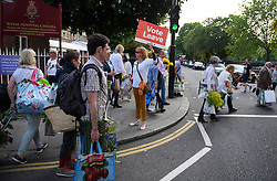 "© Licensed to London News Pictures. 28/05/2016. London, UK. A woman hold a ""VOTE LEAVE"" Eu referendum sign as Members of the public carry exhibitors' plants from the 2016 Chelsea Flower show which ended today (Sat). A wide array of unusual and striking display items can be purchased on the closing day of The Royal Horticultural Society flagship flower show,  held at the Royal Hospital in Chelsea since 1913.  Photo credit: Ben Cawthra/LNP"
