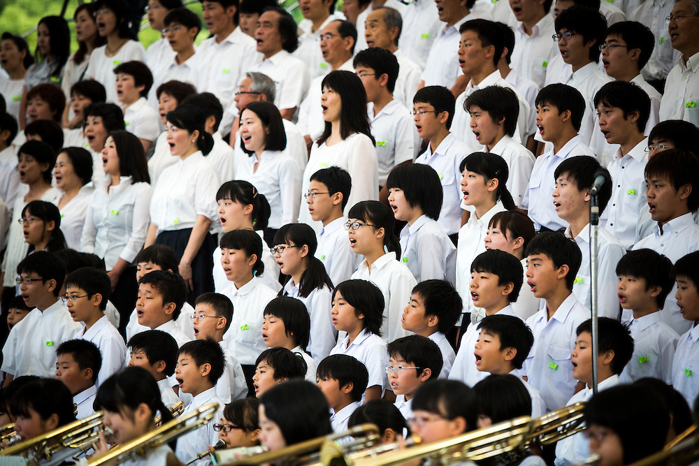 """HIROSHIMA, JAPAN - AUGUST 6 : Youth chorus singing the """"Hiroshima Peace Song"""" during the 71st anniversary of the atomic bombing on Hiroshima at Hiroshima Peace Memorial Park in Hiroshima, western Japan, Saturday, August 6, 2016. Japan marked the 71st anniversary of the atomic bombing on Hiroshima. On August 6, 1945, during World War II, the United States dropped a uranium gun-type atomic bomb named """"Little Boy"""" on the city of Hiroshima which instantly killed an estimated 80,000 people, tens of thousands more would later die of radiation exposure. Three days later, a second American B-29 bomber dropped a plutonium implosion-type bomb """"Fat Man"""" on Nagasaki, killing an estimated 40,000 people.  (Photo: Richard Atrero de Guzman/NURPhoto)"""