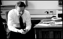 Leader of the Conservative Party David Cameron texting on his mobile phone as he waits for news in Portcullis House, Tuesday May 11, 2010. Photo By Andrew Parsons / i-Images.