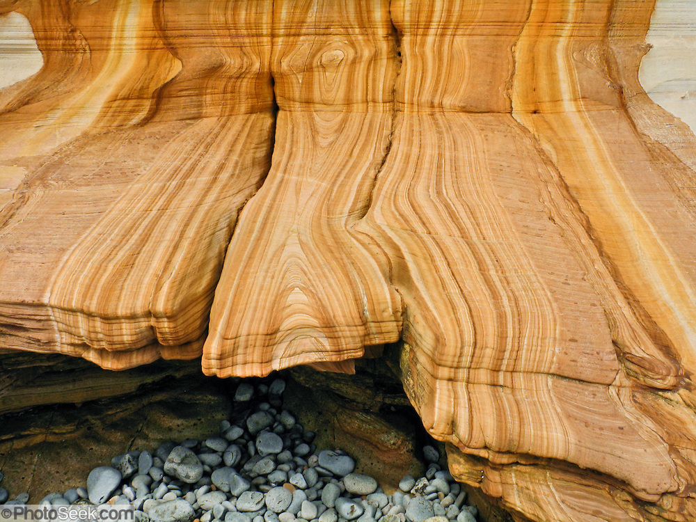Orange, yellow, brown, and white sandstone rock patterns are exposed in the Painted Cliffs of Maria Island National Park, Darlington, Tasmania, Australia. Undercut by the Tasman Sea (South Pacific Ocean), the coastal Painted Cliffs date from the Permian and Triassic, 300-200 million years ago.