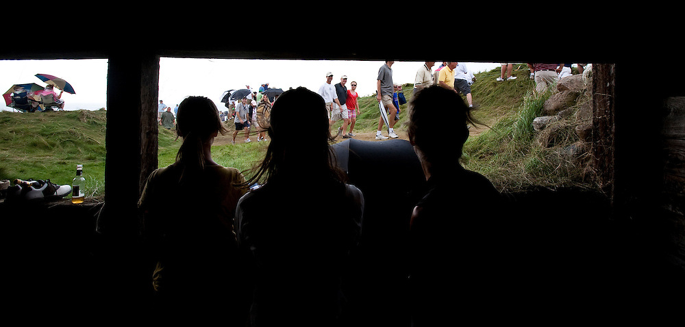 pga14, spt, lynn, 8.-Spectators take cover in a bunker behind the 6th green at Whistling Straits during the second round of the PGA Championship Friday August 13, 2010.  The wind shifted and became much stronger along with rain showers late in the day.  Photo by Tom Lynn/TLYNN@JOURNALSENTINEL.COM