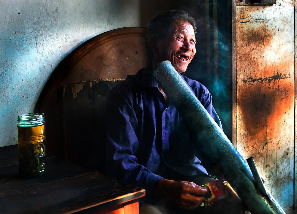 A man enjoys a smoke in a tea hous in Jianshui, Yunnan, China.