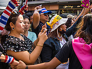05 JANUARY 2014 - BANGKOK, THAILAND: People wait to see Suthep Thaugsuband during an anti-government march in Bangkok Sunday. Suthep, leader of the anti-government protests in Bangkok, led the protestors on a march through the Chinatown district of Bangkok. Tens of thousands of people waving Thai flags and blowing whistles gridlocked what was already one of the most congested parts of the city. The march was intended to be a warm up to their plan by protestors to completely shut down Bangkok starting Jan. 13.     PHOTO BY JACK KURTZ