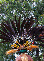 Young woman wearing a spectacular large headdress made from bird's feathers including the long black tail feathers of Princess Stephanie's Astrapia, (Astrapia stephaniae), the iridescent breastplate of the male Superb Bird-of-paradise (Lophorina superba) and the colourful feathers of lorikeets. She is also wearing animals fur. Goroka, Papua New Guinea.