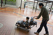 In the city famous for it's car industry a man pushes his son in a car shaped baby stroller, in the quiet shopping precint. With the local economy suffering badly from the recession, and many local jobs lost in the automobile service industries, the main shopping streets of Toyota city are quiet, in Toyota city, Japan, on Tuesday 21st April 2009.  In the first 3 months of 2009 the numbers of people seeking work at the local Toyota city 'Hello Work' employment office rose 133% compared to the first quarter of 2008. This increase is due to the jobs lost in the industries and companies which serve and supply the Toyota car company and automobile industry, for which Toyota city is famous.