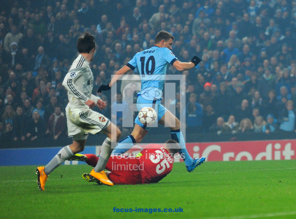CSKA Moscow goalkeeper Igor Akinfeev (below) saves a shot by Edin Dzeko of Manchester City (above) during the UEFA Champions League match at the Etihad Stadium, Manchester<br /> Picture by Greg Kwasnik/Focus Images Ltd +44 7902 021456<br /> 05/11/2014