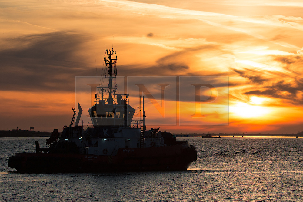 © Licensed to London News Pictures. 14/04/2015. A tug waits at Gravesend at sunrise. Tuesday 14th April got started with a deep Turneresque sky over the Thames estuary. Several days of good weather are predicted and Gravesend is often the location where the highest temperatures are recorded. Credit : Rob Powell/LNP