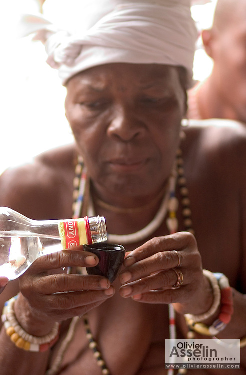 "Priestess receiving a gin offering during a ""coming out"" ceremony at a fetish shrine in Aflao, Volta Region, Eastern Ghana. A woman was released after spending three months in a small, dark room, hoping that she'd then be able to find a husband. Despite most Ghanaians being adamant followers of christianism or islam, many of them still maintain traditional beliefs. When facing a problem of any nature, some people will visit a local fetish shrine, looking for help. The main priest will consult the oracles and tell the person in need what has to be done for the problem to go away. People will typically be asked to ""serve"" the shrine for weeks, sometimes months, as their families pay the priest for their upkeep."