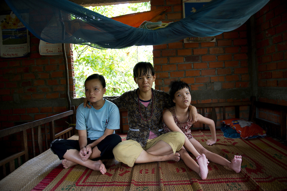 17 year old twin sisters, Tran Thu Nhuc Y and Tran Thu Vui  Mung (suffering from Dioxin poisoning), with their mother in Song Phu Village, Ben Tre Provence, Vietnam.