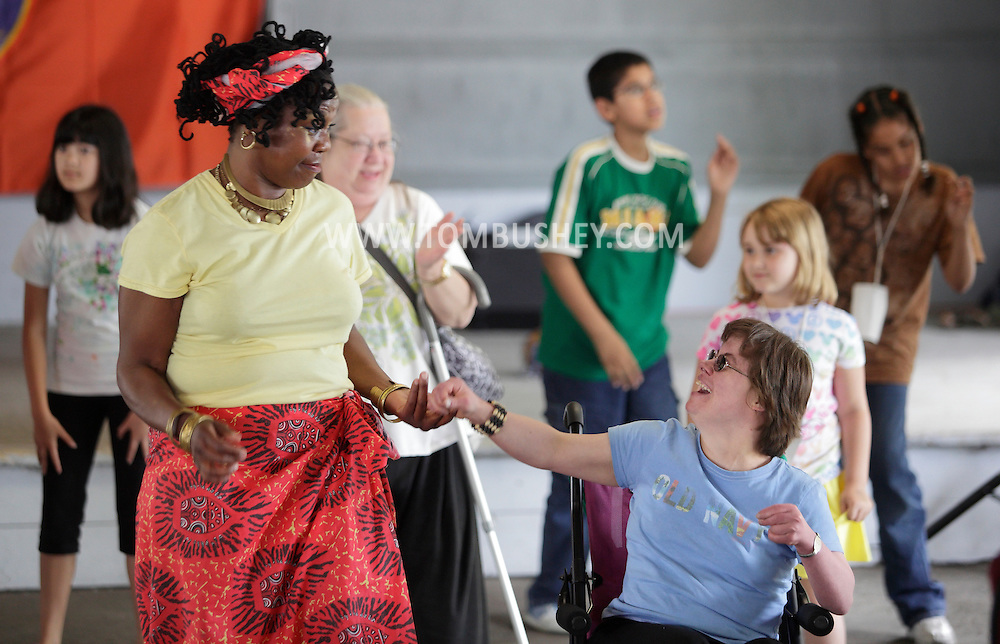 Hamptonburgh, New York - A member of the Sankofa Drum and Dance Ensemble dances with people from the audience during a performance at the fourth annual Earth & Water Festival at Thomas Bull Memorial Park on June 4, 2011.
