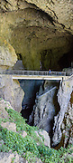 """In Slovenia, the wonderful self-guided Part 2 of Skocjan Caves walking tour follows the mysterious Reka River from Mala Dolina (Small Doline, a sinkhole) through Mahorcic Cave (Mahorciceva jama) upstream underground for 350 meters over exciting footbridges and dimly lit passages. From a large-scale karst drainage, the Reka River has carved and dissolved dramatic subterranean passages through limestone over several million years. Karst topography is a geologic formation of dissolving bedrock. Our word for """"karst"""" likely evolved from the Slovene noun kras and earlier proper noun Grast, referring to Slovenia's Karst Plateau. Visit Skocjan Caves (Skocjanske jame) Regional Park near Divaca, in the Littoral region of the Republic of Slovenia, Europe. UNESCO has honored Skocjan Caves as a World Heritage Site. This panorama was stitched from 2 overlapping photos."""