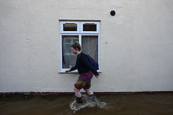 © Licensed to London News Pictures. 27/12/2015. York, UK.  A A woman wades through flood water past a window in the centre of York following heavy flooding. Large areas of the North of England have been hit by severe flooding following unusually heavy rainfall in December. Photo credit: Ben Cawthra/LNP