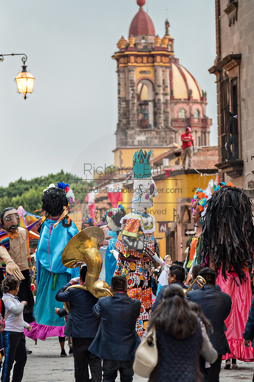 A parade of giant paper-mache puppets called mojigangas dance in a procession through the city at the start of the week long fiesta of the patron saint Saint Michael September 22, 2017 in San Miguel de Allende, Mexico.