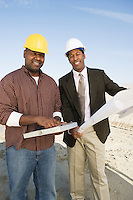 Surveyor and construction worker with blueprints, portrait