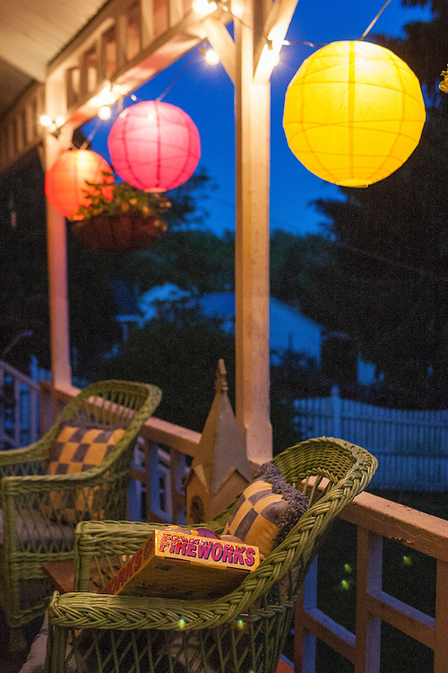 Colorful Chinese lanterns contrast against blue twilight sky on old classic porch on a summer's night