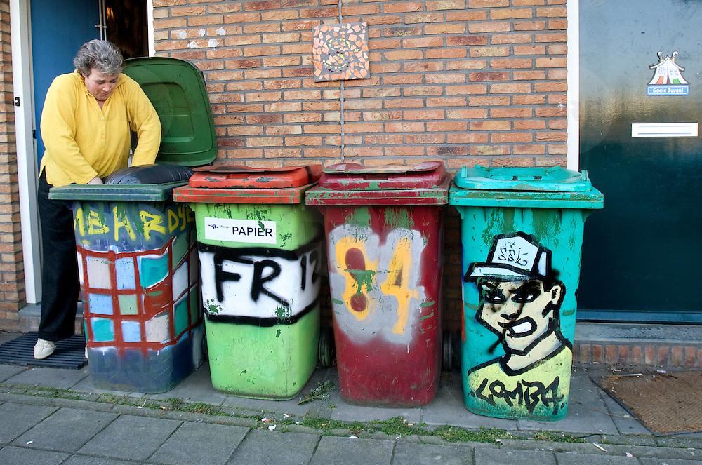 Nederland Rotterdam 19 december 2007 .Een vrouw doet afval in vuilniscontainer op de Vergiliusstraatin deelgemeente Ijsselmonde. De graffiti op de containers is aangebracht door jongeren tijdens het project 'Mensen maken de stad' van de deelgemeente om de sociale samenhang in de wijk te bevorderen. meer http://www.ijsselmonde.rotterdam.nl/smartsite.dws?ekstmode=1&id=229&goto=2088097&style=2514&items=.Vergiliusstraat.Daar was het grootste probleem het gebruik van de openbare buitenruimte. 'Sommige ouderen vonden dat de jongeren te veel overlast veroorzaakten. De jongeren vonden op hun beurt dat de ouderen te snel zeurden en de politie belden', vertelt straatbewoonster Bianca Groenhorst..?.Perspect organiseerde een middag waarin de jongeren ontwerpen konden maken voor het bespuiten van de groene kliko's in de straat. De tekening moest eerst goedgekeurd worden door de bewoner. 'Vervolgens is mijn tuin omgetoverd tot atelier en konden ze hun ontwerp in het groot op de afvalcontainer spuiten', lacht Groenhorst. Het resultaat? 'Ons stukje van de straat, de nieuwbouw, ziet er hartstikke gezellig en gekleurd uit.'.De keuze om juist met de jongeren te vergaderen was bewust. 'Wij wilden duidelijk laten zien dat zij ook hun zegje mochten doen en dat regels niet alleen door volwassenen worden opgesteld.' .'Mensen maken de stad' in IJsselmonde..Met een eigen straatagenda en budget van EUR 4500,- kan een straat, of een gedeelte daarvan, zelf activiteiten organiseren om de omgang tussen de bewoners te verbeteren en te versterken. ..De bewoners worden zelf verantwoordelijk voor het beheer van de straat, in zowel sociaal als fysiek opzicht.?.?.Hoe werkt het??Perspect start allereerst met een bewonersonderzoek in de straat, waarna een diagnose wordt opgesteld. De daarop volgende twee à drie maanden worden activiteiten georganiseerd omtrent de 'verbeterpunten'. 'Wij zetten de eerste stappen in het oplossen van de knelpunten', legt Harm de Oude van Perspect uit. 'Het uitpraten en opl