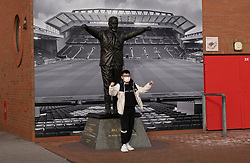 LIVERPOOL, ENGLAND - Tuesday, March 17, 2020: A supporter wearing a face mask poses for a photograph in front of a statue of former Liverpool manager Bill Shankly at a near deserted Anfield, home of Champions-elect Liverpool Football Club, after the suspension of all football due to the Coronavirus (COVID-19) and Liverpool's decision to close it's Boot Room cafe and official stores. (Pic by David Rawcliffe/Propaganda)