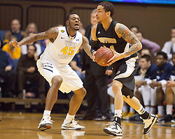 West Virginia Mountaineers forward Elijah Macon (45) plays defense against Wofford terriers forward Lee Skinner (34) during the first half at the WVU Coliseum.
