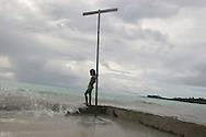 "A young girl living next to the sea in Buota village, on the South Pacific island of Kiribati, watches the sea water during a ""king tide"" wash over a wall built by her family to protect their land from erosion by the encroaching sea.The islands, and their way of life, is endangered by rising sea water levels which are eroding the fragile atoll, home to approximately 92,000 people."
