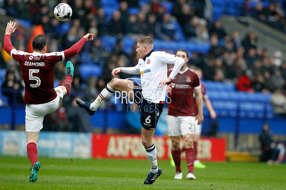 Bolton Wanderers Josh Vela (6) fliks it over Northampton Towns Zander Diamond (5) during the EFL Sky Bet League 1 match between Bolton Wanderers and Northampton Town at the Macron Stadium, Bolton, England on 18 March 2017. Photo by Craig Galloway.