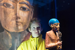 "© Licensed to London News Pictures. 01/11/2019. LONDON, UK. A staff member views ""Gilded Wooden Statue of Ptah"".  Preview of ""Tutankhamun, Treasures of the Golden Pharoah"" at the Saatchi Gallery in Chelsea.  The exhibition celebrates the 100th year anniversary of the opening of Tutankhamun's tomb and displays 150 works in the largest collection of Tutankhamun's treasures ever to leave Egypt.  The show runs 2 November to 3 May 2020.  Photo credit: Stephen Chung/LNP"