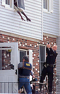MIddletown police officer Ed Jahrling, right,holds a gun on a suspect leaning out a window as other officers break into an apartment in Fairlawn Estates in Middletown during a hostage situation yesterday afternoon. (Tom Bushey photo. April 6, 2000).
