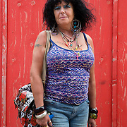 Woman with a purple patterned top photographed against a red background, in Charles Street, Sheffield