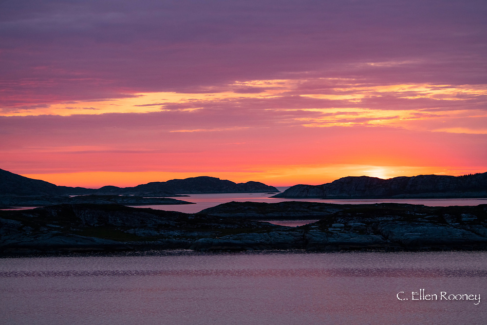 Sunset over rocky islands near Helgelandskysten on the northwest coast of Norway from a Hurtigruten ship. Norway, Europe